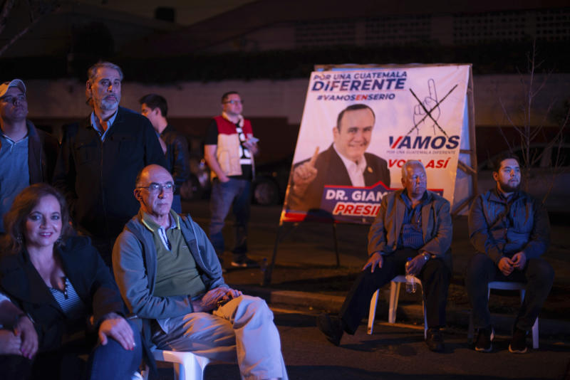 Supporters wait for Alejandro Giammattei, presidential candidate of the Vamos party, at his campaign headquarters during general elections in Guatemala City, Sunday, June 16, 2019. (AP Photo/Santiago Billy)