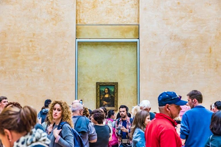 Crowd of tourists in front of Mona Lisa on gallery wall.