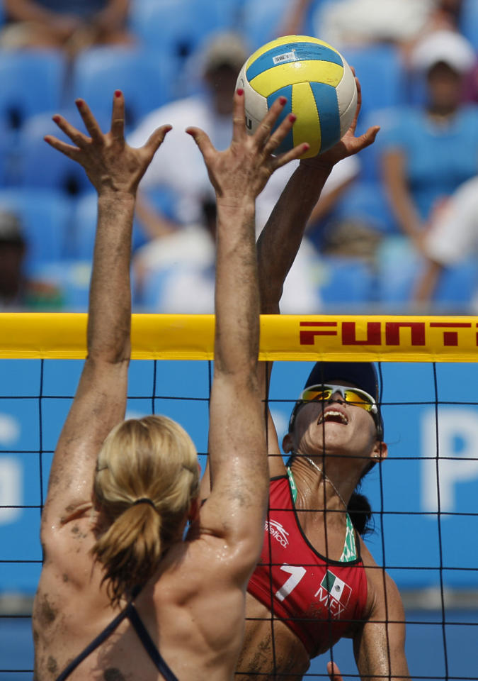 Mexico's Mayra Garcia, right, reaches for the ball during a women's beach volleyball semifinal match against the United States at the Pan American Games in Puerto Vallarta, Mexico, Thursday Oct. 20, 2011. (AP Photo/Ariana Cubillos)