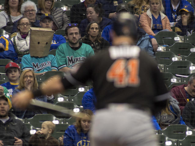 A Miami Marlins fan wears a bag over his head as Miami Marlins' Justin Bour strikes out against the Milwaukee Brewers to end the eighth inning of a baseball game Friday, April 20, 2018, in Milwaukee. (AP Photo/Darren Hauck)