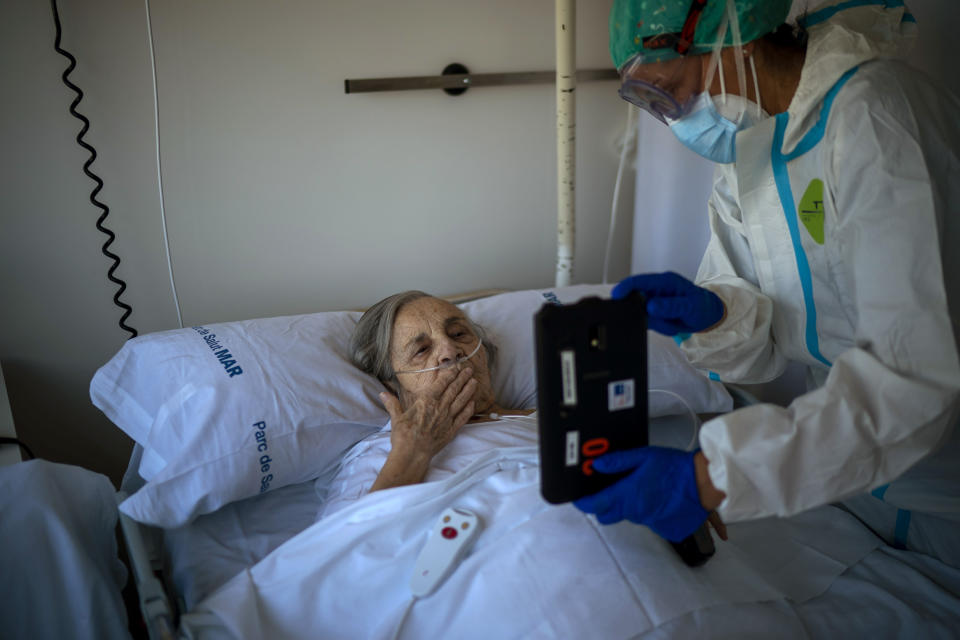 Nurse Marta Fernandez holds up a tablet computer over the chest of 94-year-old Maria Teresa Argullos Bove so that she can speak to her sister, children and grandchildren from her hospital bed at the COVID-19 ward at the hospital del Mar in Barcelona, Spain, Wednesday, Nov. 18, 2020.(AP Photo/Emilio Morenatti)
