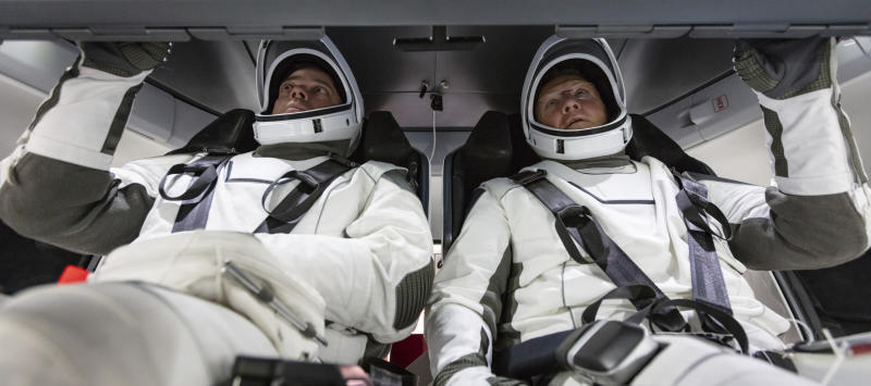 In this August 2018 photo made available by SpaceX, NASA astronauts Doug Hurley and Bob Behnken familiarize themselves with SpaceX's Crew Dragon, the spacecraft that will transport them to the International Space Station as part of NASA's Commercial Crew Program, at the Kennedy Space Center in Cape Canaveral, Fla. (SpaceX via AP)
