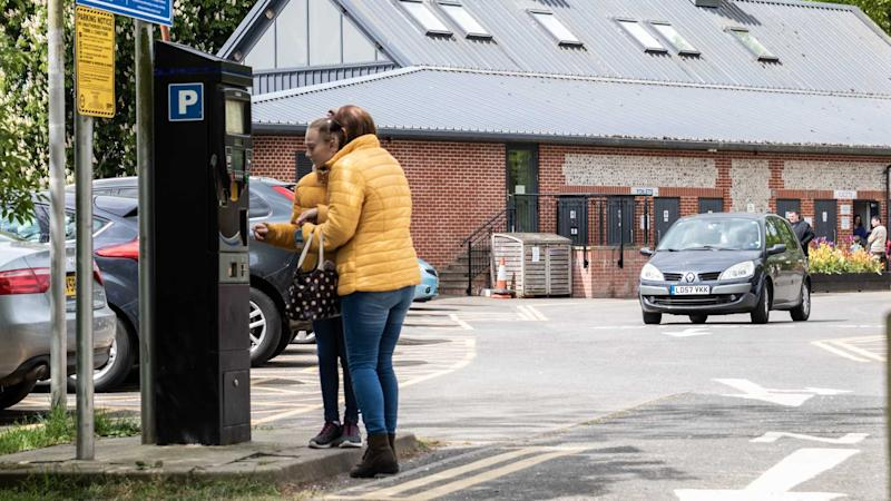 Women paying for parking at pay and display car park in Arundel West Sussex UK