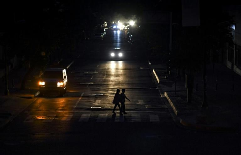 People are silhouetted by the lights of a vehicle as they cross a street in Caracas as the capital and other parts of Venezuela were hit by a massive power cut (AFP Photo/Yuri CORTEZ)