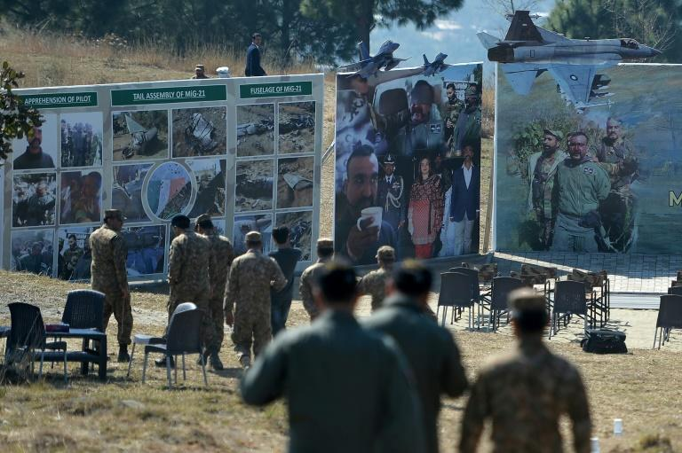 Pakistani soldiers walk on February 26 near images of captured Indian pilot Abhinandan Varthaman at Horran village, where his aircraft was shot down