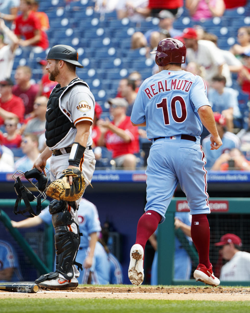 Philadelphia Phillies' J.T. Realmuto, right, comes in to score on the hit by Jake Arrieta as San Francisco Giants catcher Stephen Vogt, left, looks on during the second inning of a baseball game, Thursday, Aug. 1, 2019, in Philadelphia. (AP Photo/Chris Szagola)