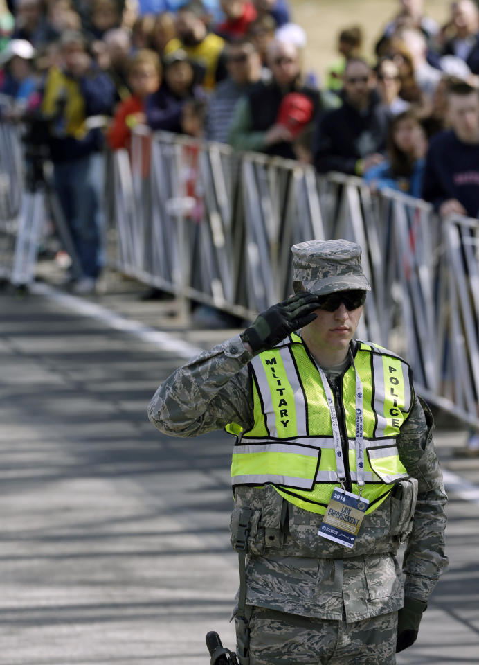 A military police officer salutes during opening ceremonies of the 118th Boston Marathon Monday, April 21, 2014 in Hopkinton, Mass. (AP Photo/Steven Senne)