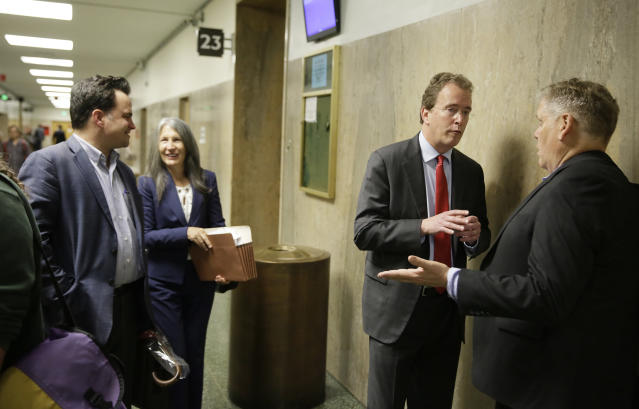 """In this photo taken Tuesday, May 21, 2019, from left, David Snyder, an attorney with the First Amendment Coalition, attorney Duffy Carolan, and Thomas Burke, attorney for freelance journalist Bryan Carmody, talk outside a courtroom before a hearing in San Francisco. Advocates of the press pushed back against a San Francisco police chief who said a freelance journalist had """"crossed the line"""" in conspiring to steal a police report, saying that it is not a crime to disclose a public record. Carolan, who is representing several media organizations siding with the independent reporter, says that the public has constitutional rights to access public records. (AP Photo/Eric Risberg)"""