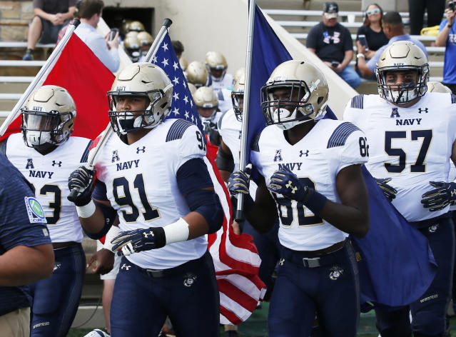 Navy defensive end Tyler Sayles (91) leads his team onto the field carrying the flag before an NCAA college football game against Tulsa in Tulsa, Okla., Saturday, Sept. 30, 2017. (AP Photo/Sue Ogrocki)