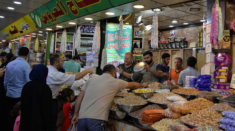 Iraqis shop for nuts, sweets, and dried fruits at a market on the last day of the Muslim holy month of Ramadan before the Eid al-Fitr holiday on June 14, 2018 (AFP Photo/Zaid AL-OBEIDI)