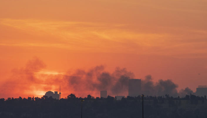 Smoke covers the Johannesburg skyline as people protests in downtown area, in Johannesburg, South Africa, Sunday, July 11, 2021. Protests have spread from the KwaZulu Natal province to Johannesburg against the imprisonment of former South African President Jacob Zuma who was imprisoned last week for contempt of court. (AP Photo/Themba Hadebe)