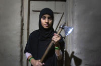 Kashmiri girl Muskan, 14, displays outside her home an axe that the family carries with them when they go outdoors at night to protect themselves from wild animals, at Dardkhor village, outskirts of Srinagar, Indian controlled Kashmir, Monday, Aug. 24, 2020. Amid the long-raging deadly strife in Indian-controlled Kashmir, another conflict is silently taking its toll on the Himalayan region's residents: the conflict between man and wild animals. According to official data, at least 67 people have been killed and 940 others injured in the past five years in attacks by wild animals in the famed Kashmir Valley, a vast collection of alpine forests, connected wetlands and waterways known as much for its idyllic vistas as for its decades-long armed conflict between Indian troops and rebels. (AP Photo/Mukhtar Khan)