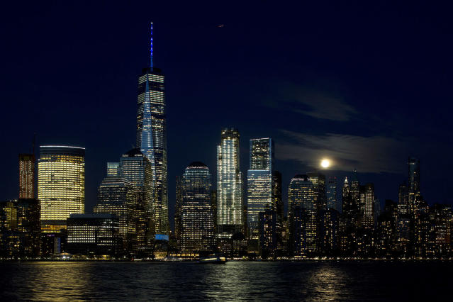 <p>A full moon rises above the New York skyline and the Hudson River, May 10, 2017, seen from Jersey City, N.J. One World Trade Center towers above the other buildings. (Photo: Mark Lennihan/AP) </p>