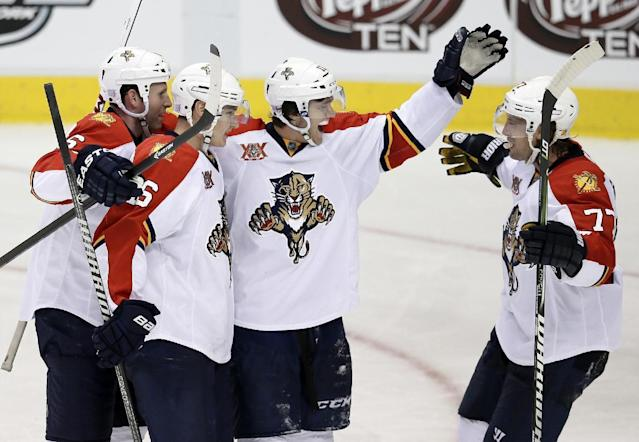Florida Panthers' Ryan Whitney, left, Aleksander Barkov, Jonathan Huberdeau (11) and Tom Gilbert (77) celebrate a goal by Barkov against the Dallas Stars in the third period of an NHL hockey game, Thursday, Oct. 3, 2013, in Dallas. The Panthers won 4-2. (AP Photo/Tony Gutierrez)