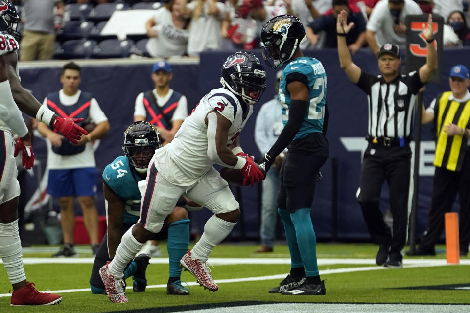 Houston Texans running back Mark Ingram II (2) runs for a touchdown as Jacksonville Jaguars' Damien Wilson (54) and CJ Henderson (23) defend during the first half of an NFL football game Sunday, Sept. 12, 2021, in Houston. (AP Photo/Sam Craft)
