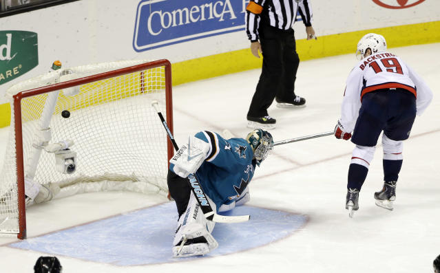 Washington Capitals' Nicklas Backstrom, right, of Sweden, scores the game-winning goal past San Jose Sharks goalie Antti Niemi, of Finland, during a shootout in an NHL hockey game on Saturday, March 22, 2014, in San Jose, Calif. Washington won 3-2. (AP Photo/Marcio Jose Sanchez)