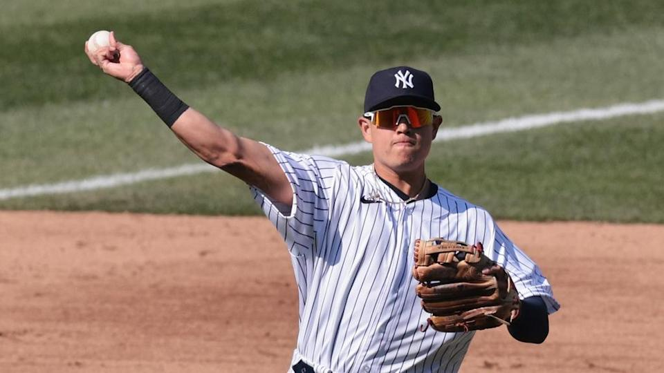 Gio Urshela makes throw with sunglasses on in pinstripes