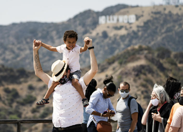 Some visitors wear face masks outdoors while taking pictures of the Hollywood sign at the Griffith Observatory in Los Angeles, Monday, May 17, 2021. California is keeping its rules for wearing face masks in place until the state more broadly lifts its pandemic restrictions on June 15. (AP Photo/Damian Dovarganes)
