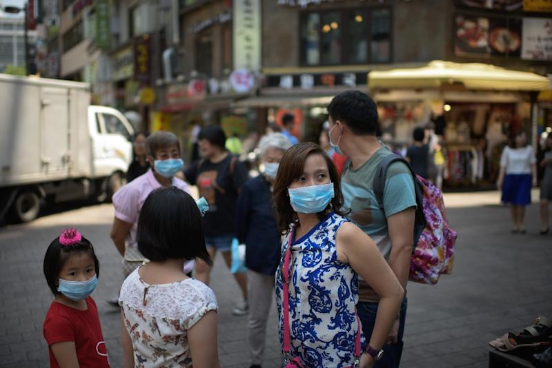 A family of tourists wearing face masks stand on a street in the popular Myeongdong shopping area in Seoul, on June 4, 2015 (AFP Photo/Ed Jones)