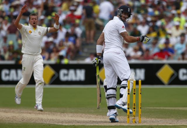England's Kevin Pietersen looks at the stumps after he was bowled out by Australia's Peter Siddle (L) during the fourth day of the second Ashes test cricket match at the Adelaide Oval December 8, 2013. REUTERS/David Gray (AUSTRALIA - Tags: SPORT CRICKET)