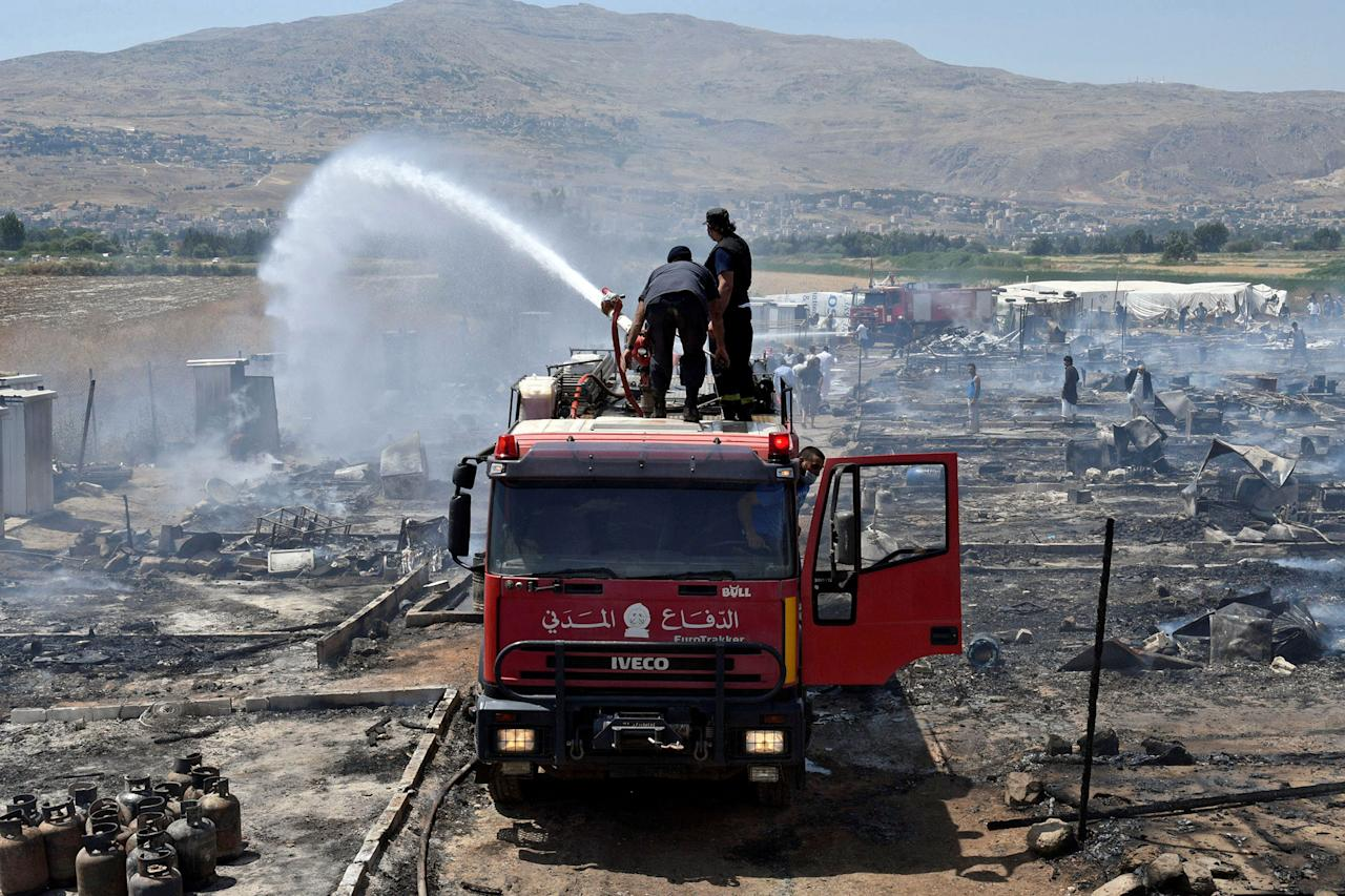 <p>Civil defence members put out fire at a camp for Syrian refugees near the town of Qab Elias, in Lebanon's Bekaa Valley, July 2, 2017. (Hassan Abdallah/Reuters) </p>