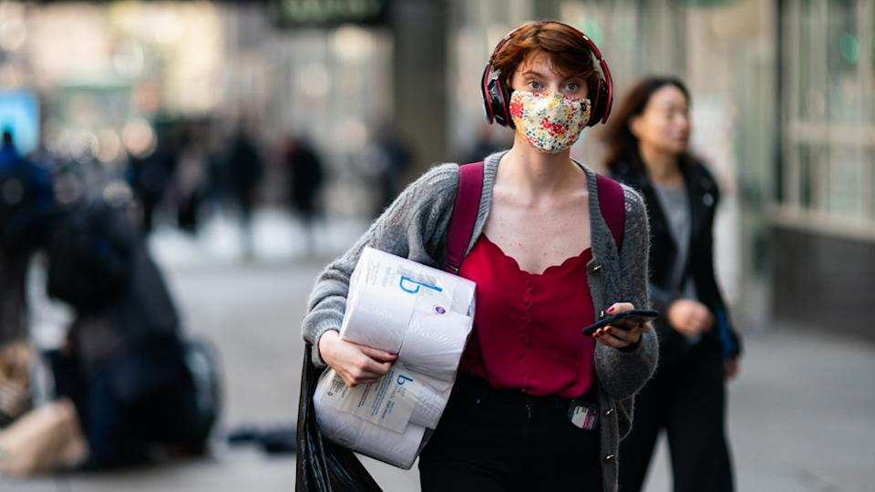 A woman wearing a mask carrying toilet paper during the coronavirus pandemic.
