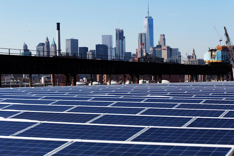 The Manhattan skyline peers over a rooftop covered with solar panels at the Brooklyn Navy Yard in New York. (Photo: ASSOCIATED PRESS)