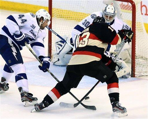 Ottawa Senators' Peter Regin (13) attempts to shoot the puck as he is checked by Tampa Bay Lightning center Nate Thompson and goaltender Cedrick Desjardins watches during the second period of their NHL hockey game in Ottawa, Ontario, Saturday, March 23, 2013. (AP Photo/The Canadian Press, Fred Chartrand)