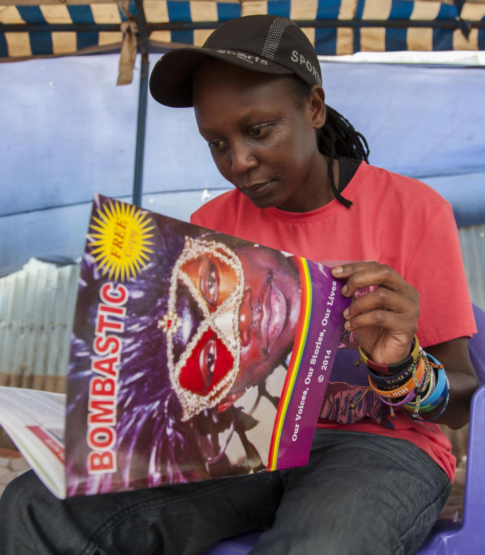"""Gay rights activist Kasha Jacqueline Nabagesera looks at a copy of Bombastic, which was launched in December as MPs were vowing to introduce a new anti-gay bill as a """"Christmas present"""" (AFP Photo/Isaac Kasamani)"""