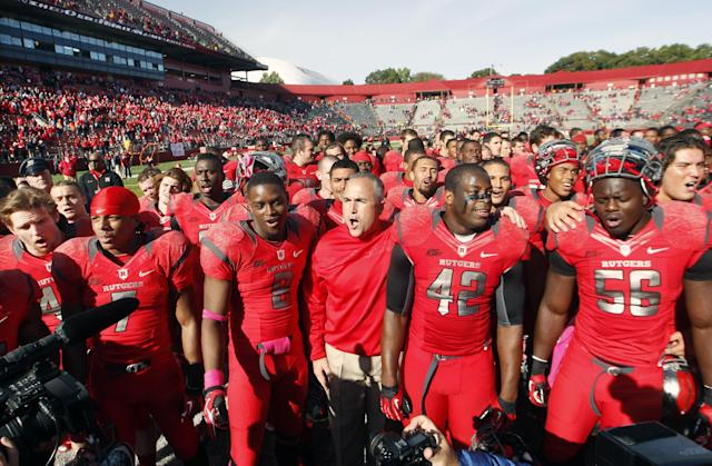FILE - In this Oct. 13, 2012, photo, Rutgers coach Kyle Flood, center, stands with his players as they sing Rutgers' alma mater after defeating Syracuse in an NCAA college football game in Piscataway, N.J. Rutgers has gone a respectable 53-36 with six bowl appearances in football since 2007, when it dropped six sports, and attendance at High Point Solutions Stadium has averaged more than 45,000, a number that's still short of the new seating capacity of 52,454 that came with a $102 million expansion completed in 2009. (AP Photo/Mel Evans, File)