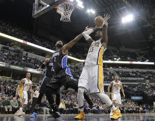 Orlando Magic's Kyle O'Quinn (2) and Indiana Pacers' Roy Hibbert (55) reach for a rebound during the first half of an NBA basketball game Tuesday, March 19, 2013, in Indianapolis. (AP Photo/Darron Cummings)