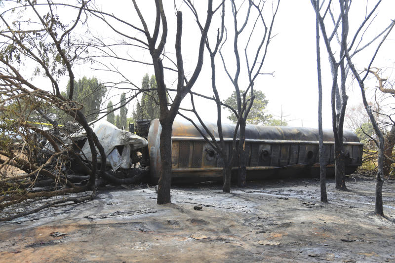 The wreckage of petrol tanker lies among burnt out trees in Morogoro Township about 200 km from Dar es Salaam, Saturday Aug. 10, 2019. A damaged tanker truck exploded in eastern Tanzania Saturday as people were trying to siphon fuel out of it, killing at least 62, in one of the worst incidents of its kind in the East African country. (AP Photo/ Khalfan Said)