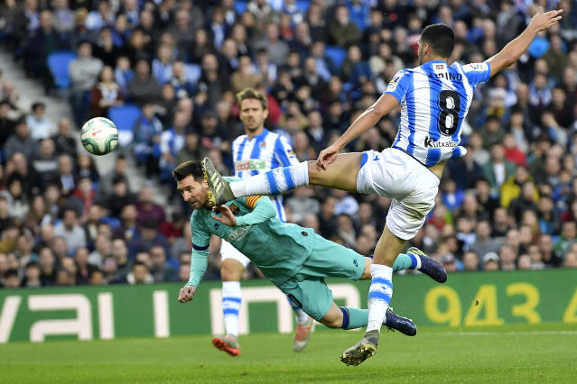 Real Sociedad's Mikel Merino, right, leaps to block a header from Barcelona's Lionel Messi during the Spanish La Liga soccer match between Real Sociedad and Barcelona, at Anoeta stadium, in San Sebastian, Spain, Saturday, Dec. 14, 2019. (AP Photo/Alvaro Barrientos)