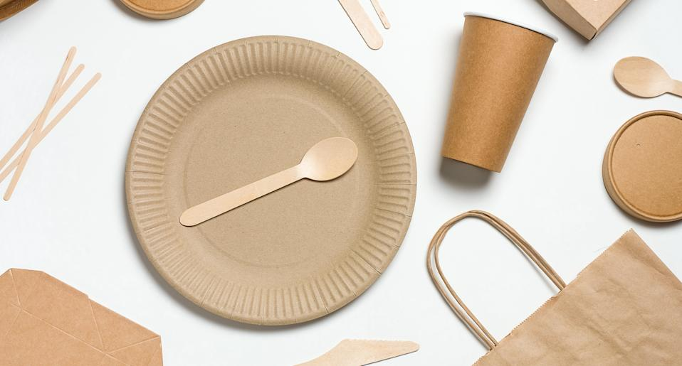 Disposable tableware made of bamboo wood and paper on a white background. The photo is covered in graininess and noise.