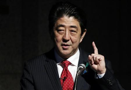 Japan's PM Abe gestures as he gives a keynote address at Japan Summit 2014 hosted by the Economist magazine in Tokyo