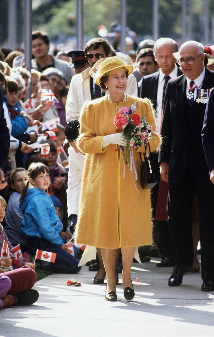 For a walkabout in Queen's Park, Her Majesty stood out from the crowd in a punchy yellow mohair coat and co-ordinating hat. <em>[Photo: Getty]</em>