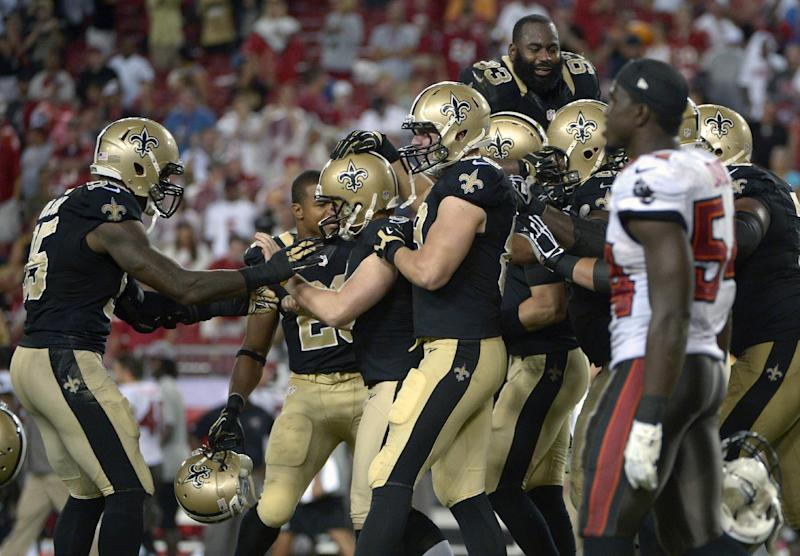 New Orleans Saints kicker Garrett Hartley, second from left, is swarmed by teammates linebacker Martez Wilson, left, and Josh Hill, center, as Tampa Bay Buccaneers outside linebacker Lavonte David (54) walks off the field after Hartley kicked the game-winning field goal as time ran out at the end of an NFL football game in Tampa, Fla., Sunday, Sept. 15, 2013.(AP Photo/Phelan M. Ebenhack)