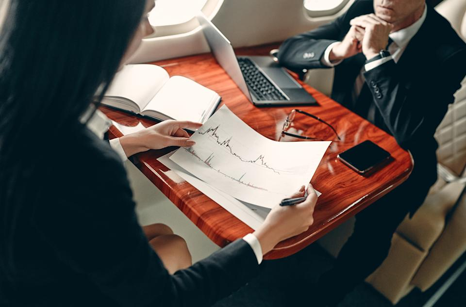 Business people in private jet. Young business woman and senior business man working while flying in aircraft. Successful work partners.
