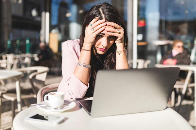 A frustrated woman holds her head as she looks at a laptop