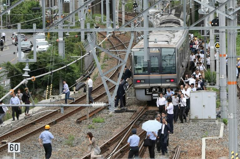 Passengers walk along railroad tracks following the quake