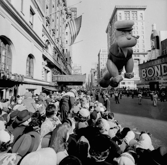 <p>Helium-filled Popeye balloon figure floats above some of the 1,300,000 persons watching the 33rd Macy's Thanksgiving Day Parade pass through Times Square, New York, Nov. 26, 1959. (Photo: AP) </p>