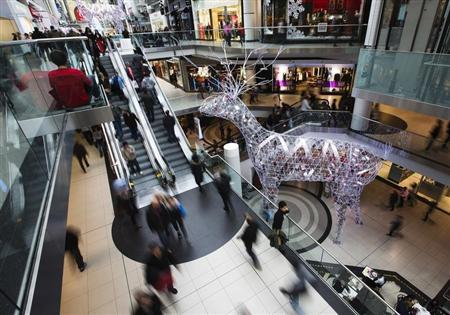 People shop in the Eaton Centre shopping mall as they walk by a giant reindeer Christmas decoration in Toronto