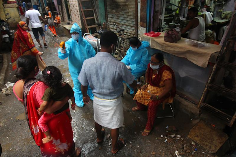 Healthcare workers wearing personal protective equipment (PPE) conduct a medical check-up at a slum in Mumbai, India on August 28, 2020. India is the third worst-hit nation by the Coronavirus (COVID-19) pandemic after the United States and Brazil. (Photo by Himanshu Bhatt/NurPhoto via Getty Images)