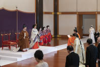 In this photo provided by the Imperial Household Agency of Japan, Japan's Crown Prince Akishino, in orange robe, flanked by his wife Crown Princess Kiko, attends a ceremony for formally proclaims Akishino is the first in line to the Chrysanthemum Throne, in front of Emperor Naruhito, left, and Empress Masako, second from left, at the Imperial Palace in Tokyo, Sunday, Nov. 8, 2020. Akishisho, Naruhito's younger brother, was formally sworn in as first in line to the Chrysanthemum Throne in a traditional palace ritual that has been postponed for seven month and scaled down due to the coronavirus pandemic. (Imperial Household Agency of Japan via AP)