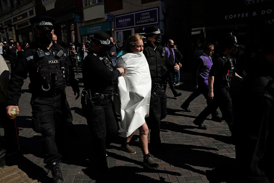 """A topless protester who shouted """"save the planet"""", is taken away by police officers after they put a cover over her body outside Windsor Castle during the funeral of Britains Prince Philip in Windsor, England."""