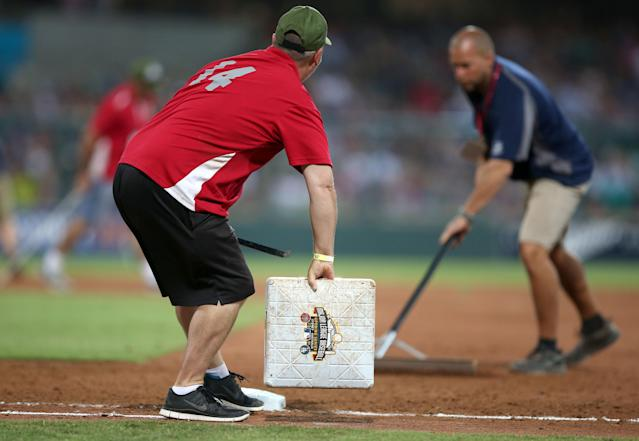 Grounds crew change the bases during the Major League Baseball opening game between the Los Angeles Dodgers and Arizona Diamondbacks at the Sydney Cricket ground in Sydney, Saturday, March 22, 2014. (AP Photo/Rick Rycroft)