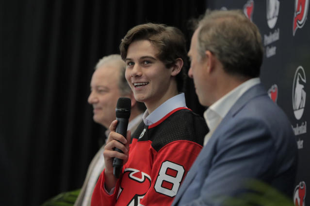 New Jersey Devils forward Jack Hughes, center, the No. 1 overall pick in the 2019 NHL draft, takes questions during a news conference introducing the prospect to local media, Tuesday, June 25, 2019, in Newark, N.J. (AP Photo/Julio Cortez)