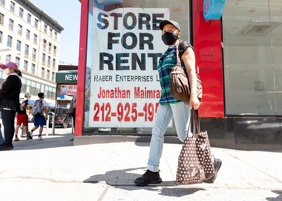 NEW YORK, NEW YORK - MAY 27: A person walks by an empty store in China Town on May 27, 2021 in New York City. On May 19, all pandemic restrictions, including mask mandates, social distancing guidelines, venue capacities and restaurant curfews were lifted by New York Governor Andrew Cuomo.  (Photo by Noam Galai/Getty Images)