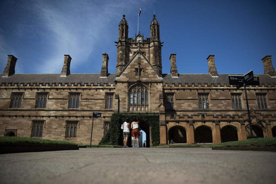 Two students stand in the University of Sydney's quad.
