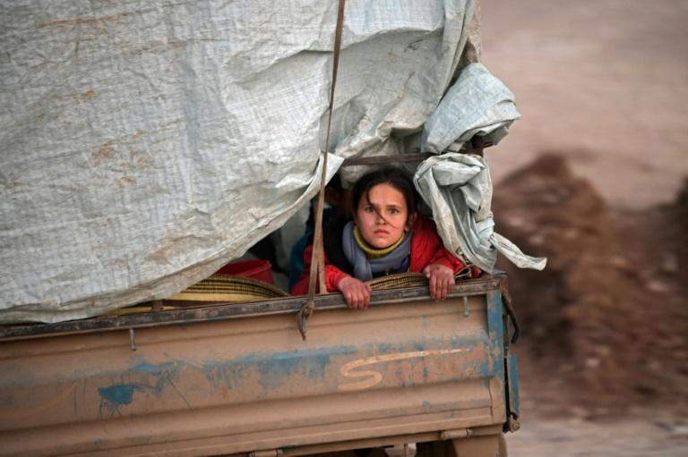 A displaced Syrian girl rides in the back of a truck on the way to Deir al-Ballut camp along the border with Turkey, which is eager to prevent another flood of refugees into its territory
